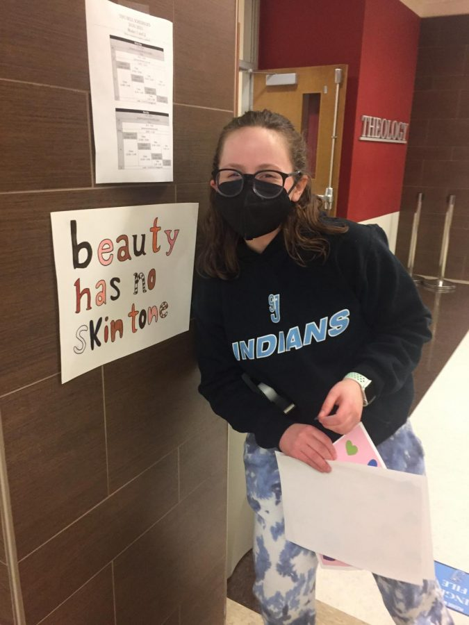 SADD Club member Luci Flanagan poses with a skin color positivity poster she's hung up. Photo credit Lauren Eggleston.