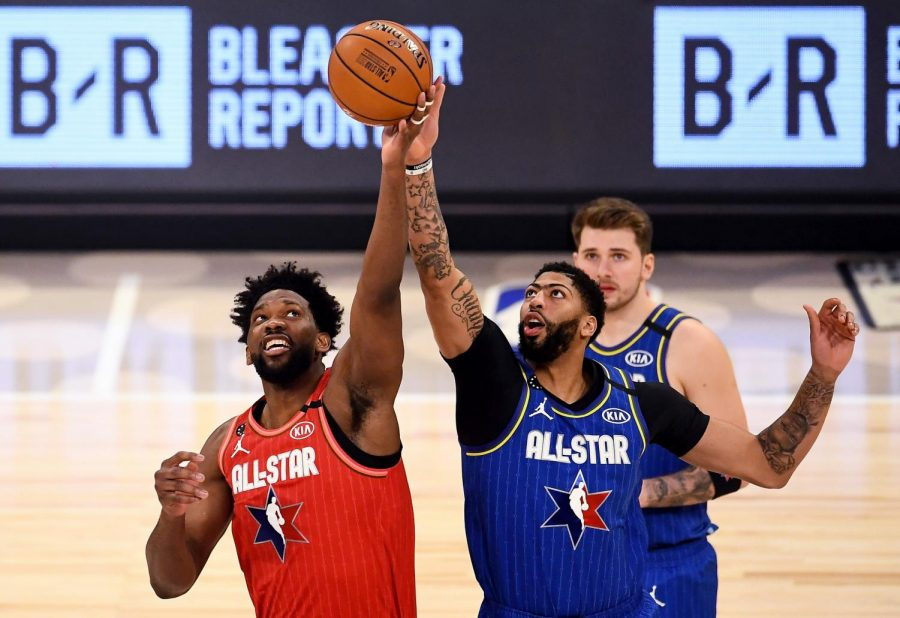 Joel Embiid (seen in red) and Anthony Davis (seen in blue) reach for a jump ball in the 2020 All-Star Game.