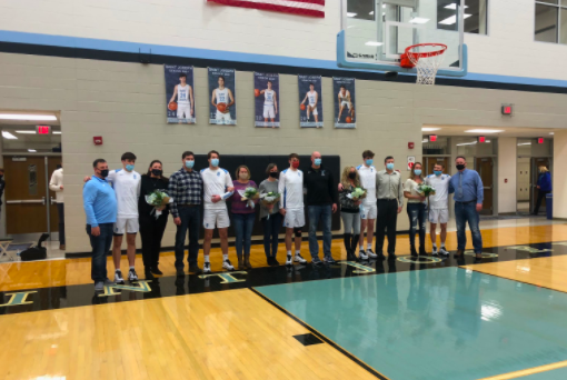 All five senior boys standing with their parents, being honored before the big game against Washington.