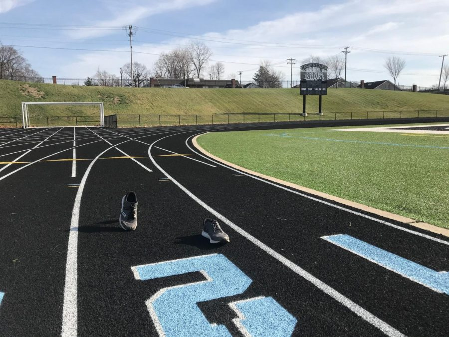 The track at Father Bly Field with a pair of sneakers in the middle of running.