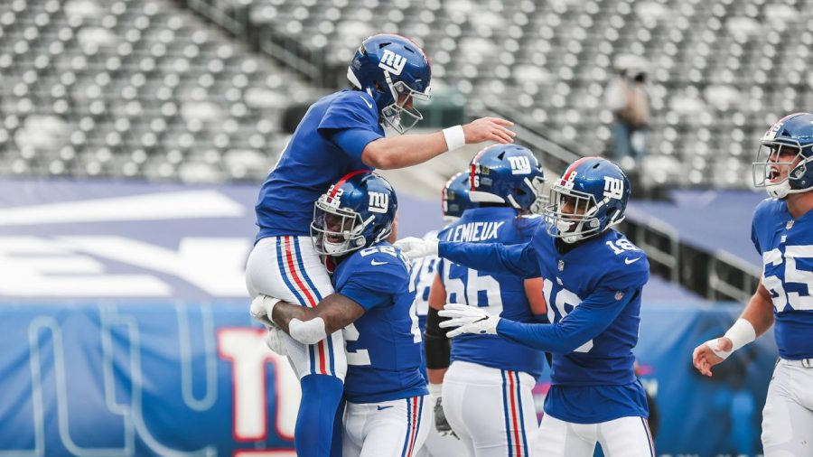 Daniel+Jones+and+the+Giants+offense+celebrate+a+touchdown+in+an+empty+Metlife+Stadium.