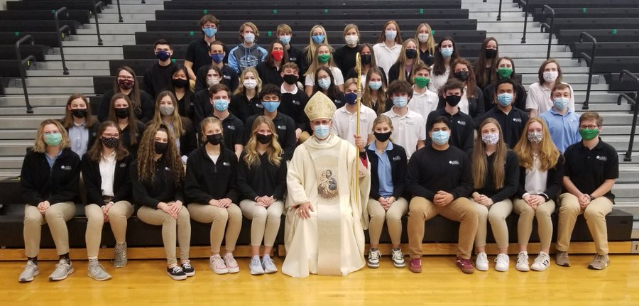 The+seniors+of+the+Saint+Joe+Class+of+2021+sit+with+Bishop+Kevin+C.+Rhoades+after+they+are+recognized+at+all+school+mass.+